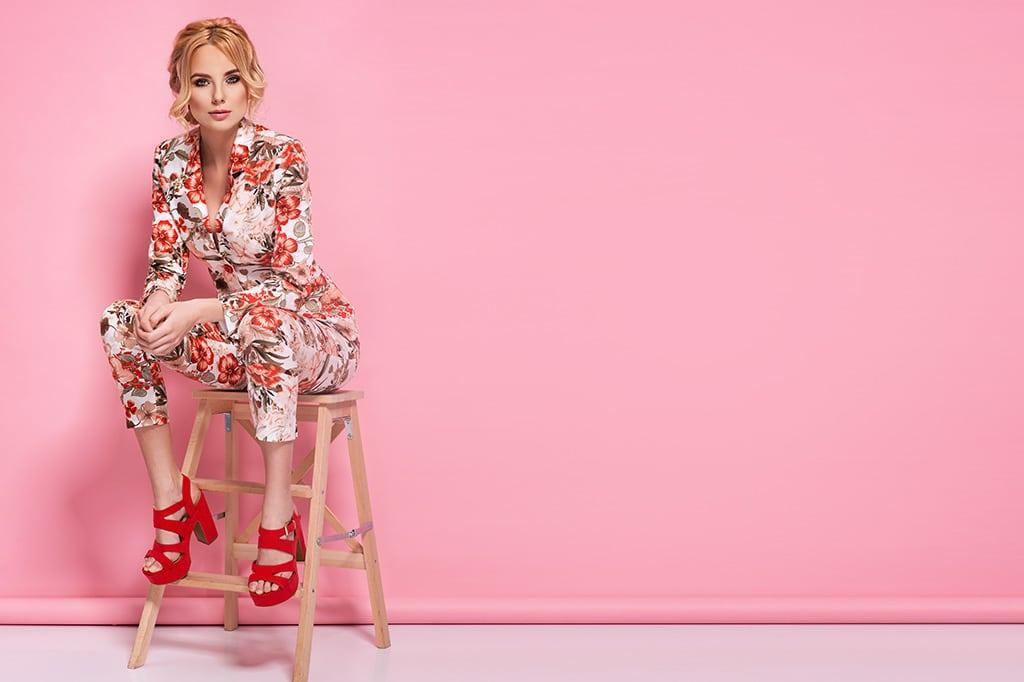 jeune femme assise sur une chaise avec fond rose